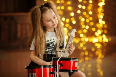 Little pretty girl with toy guitar and drums before bokeh background