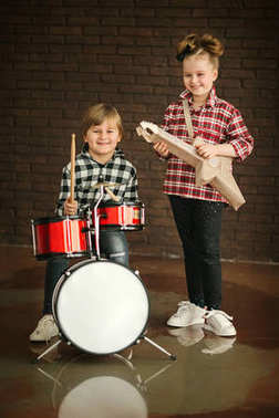 Little pretty girl and nice boy with toy guitar and drums before brick wall