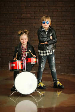 Little pretty girl and nice boy in leather jackets with toy drums before brick wall