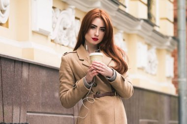 Beautiful red-hair girl look at the camera, smile and listening to music. Coffee time.