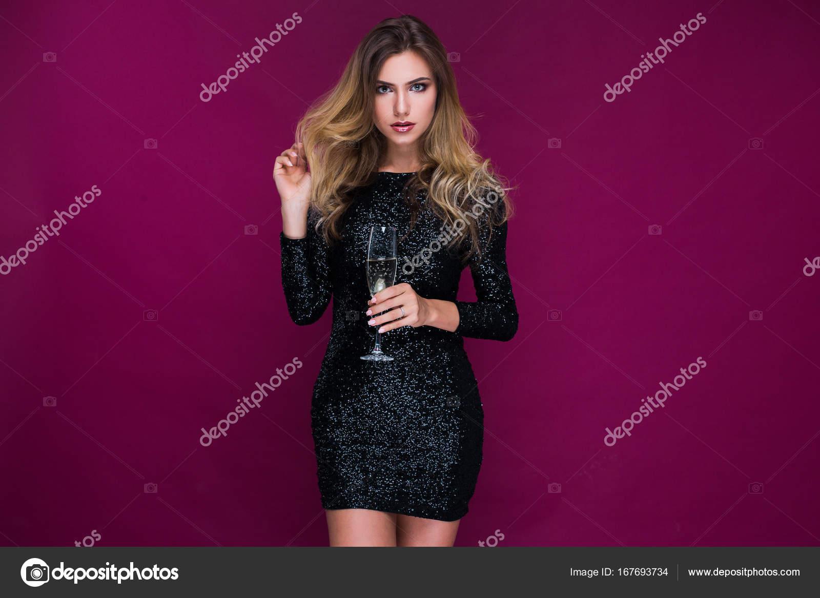 Joven atractiva y sexy en sexy vestido brillante con Copa de champán ...