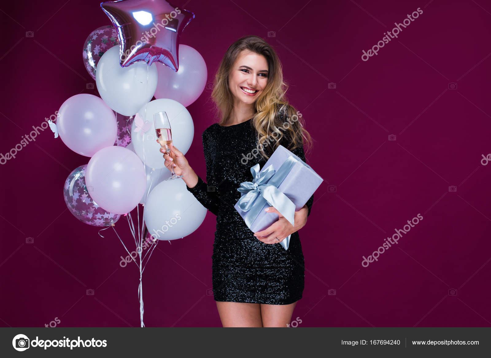 Hermosa mujer feliz rubia en sexy vestido corto con regalo y Copa de ...