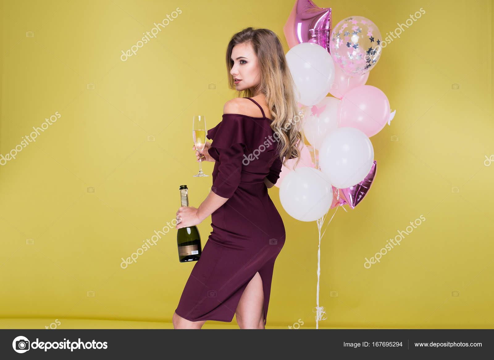 Schöne und attraktive Frau in Marsala Kleid mit Flasche und Glas ...