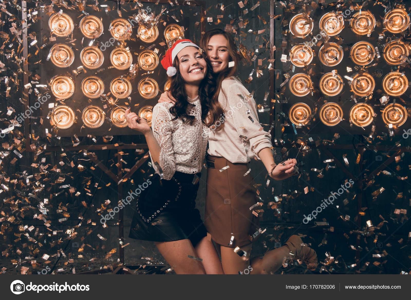 Kerstmuts Met Licht : Twee gelukkige mooie meisjes in kerstmuts met bengalen licht