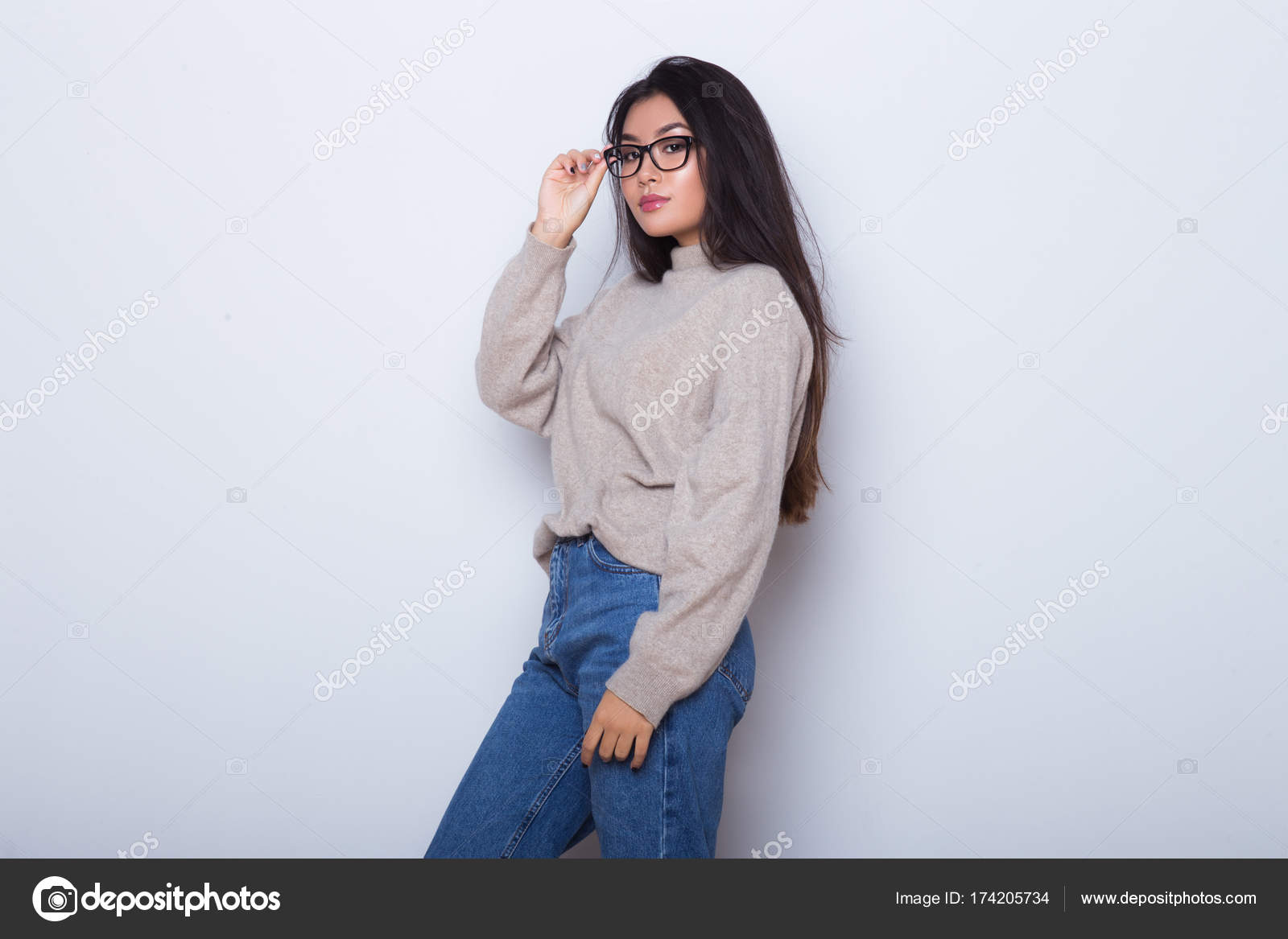 000a3a43f97 Young Asian girl hipster posing in glasses on her eyes in front of white  wall fashion portrait