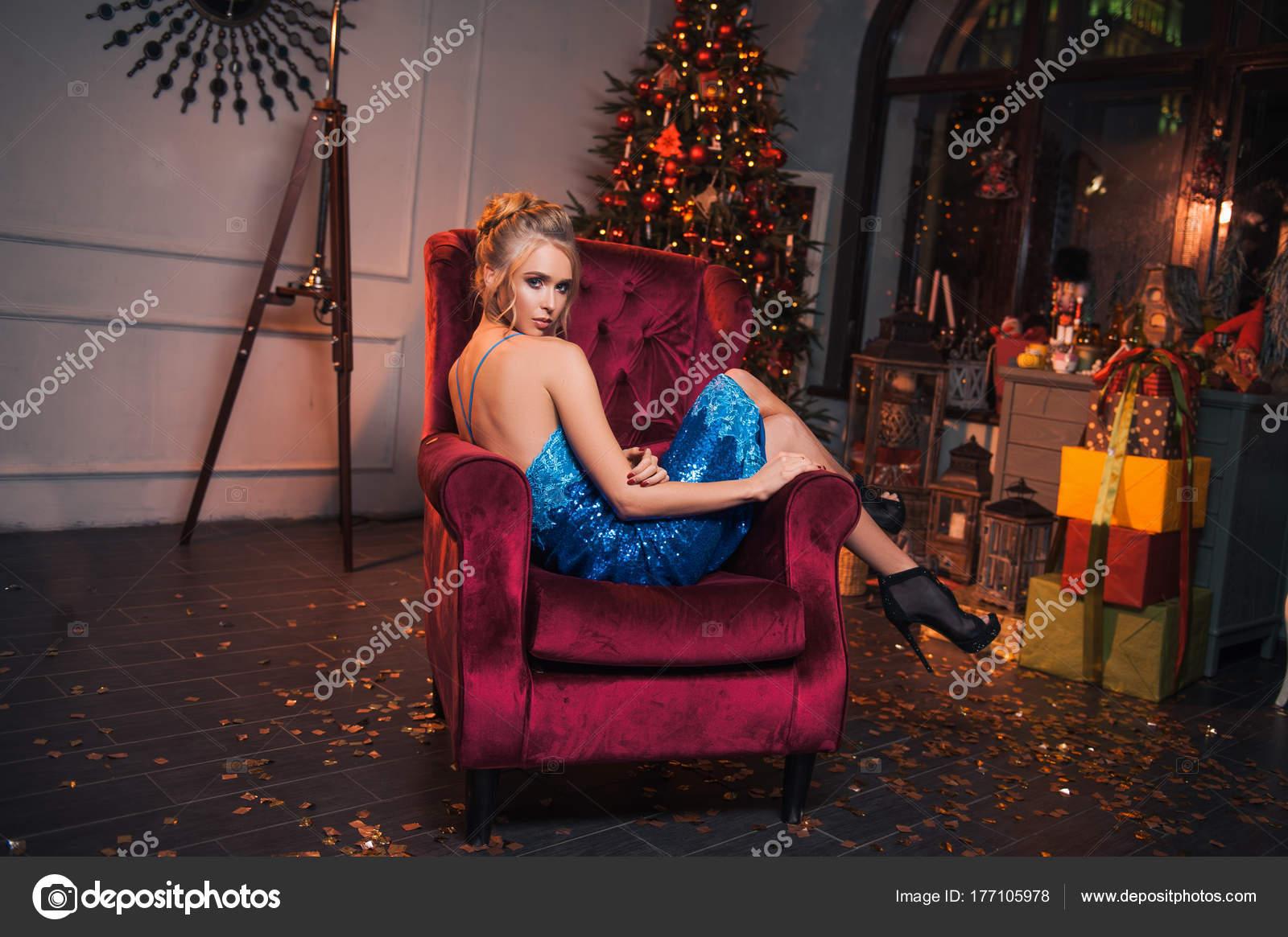 Schöne sexy Frau in dem roten Stuhl sitzen. Blonde Glamour-Girl in ...