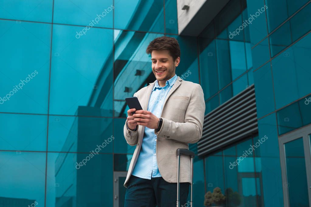 Achieving his success! Smiling handsome young man on business trip text business messaging from his cell phone to inform his colleagues of having reached their goal.