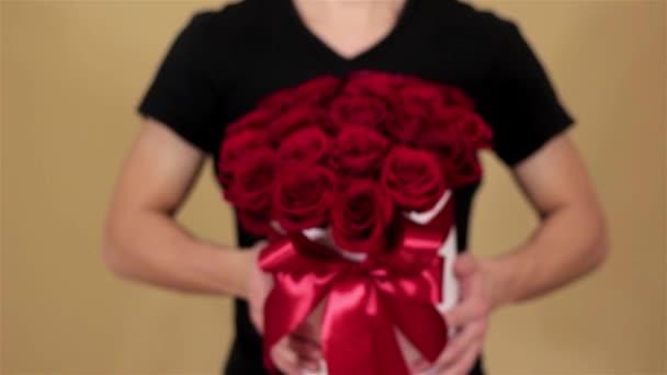Muž v černé tričko drží v ruce bohatý dar kytice 21 červených růží. Složení květiny v bílé klobouky. Remizoval s širokou červenou stuhu a luk. V pomalém pohybu