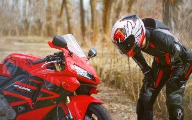 KRASNOYARSK, RUSSIA - April 21, 2018: Beautiful motorcyclist in full gear and helmet on a red and black Honda 2005 CBR 600 RR (PC37).