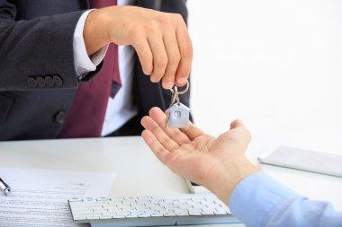 Man in suit offering a key