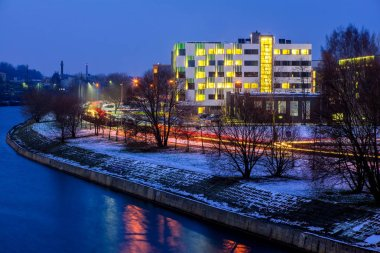 Modern design of office  building. Modern architecture in twilight. Snow and river.