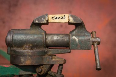 Vice grip tool squeezing a plank with the word cheat