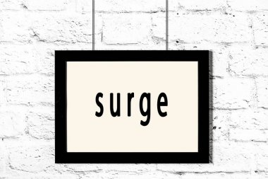 Black frame hanging on white brick wall with inscription surge