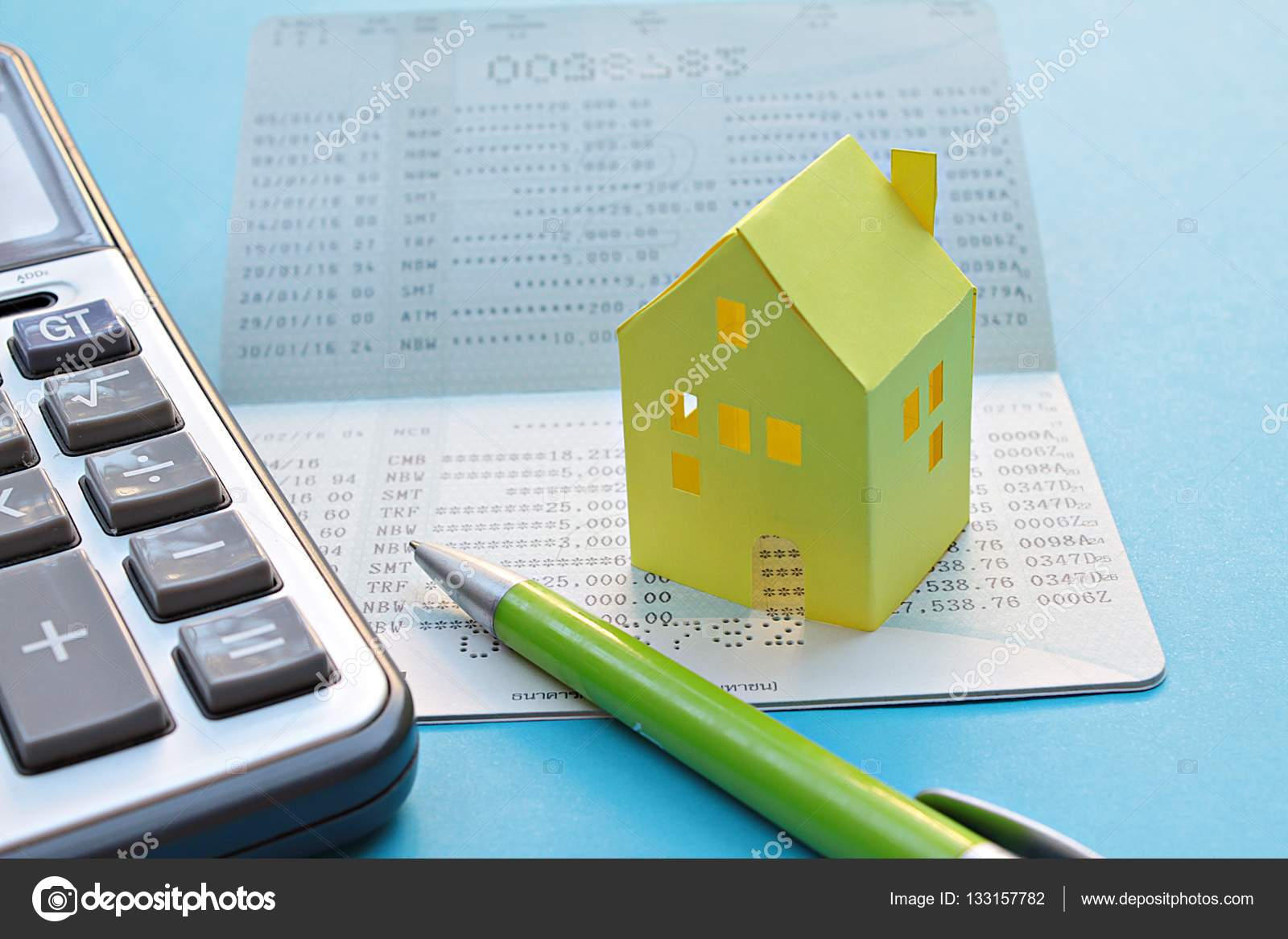 Savings account passbook, calculator, pen and yellow paper house ...
