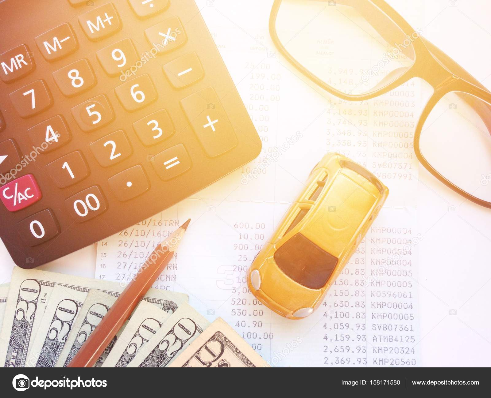 Miniature car model, pencil, calculator, eyeglasses, money and ...