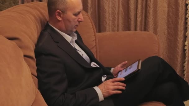 Businessman with tablet sitting on the sofa.