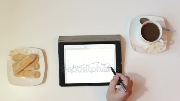 Businessman analyzes the data exchange on the tablet.