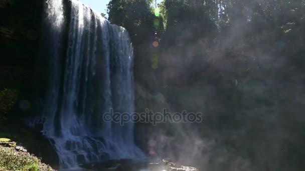 Zblízka pohled na vodopád v deštném pralese. Vodní mlha stoupá. HD se zvukem. Světlo za tropických stromů. Vysoká vlhkost v džungli. Divoké vegetace má mnoho stromů. Odpočinek pro turisty na šířku.
