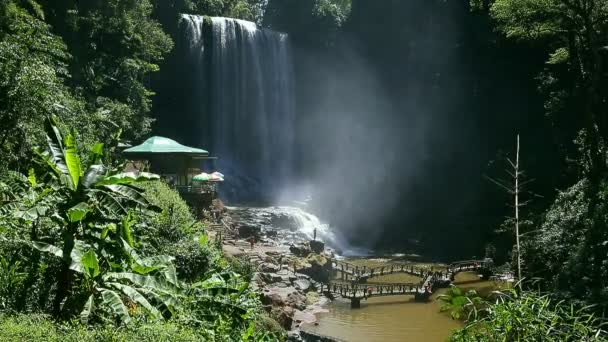 Wasserfall im Dschungel und Touristen. Der Wind bläst. Dichte grüne Bäume. Gras, Blätter und Baumstämme in den Tropen. Der Dschungel Asiens. sonniger Sommertag im Dschungel. Wind erschüttert Äste von Bäumen.
