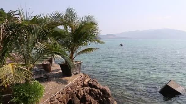 Stone island in ocean. Boat on horizon of sea.