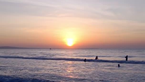 Nuotatori nel mare al tramonto alba