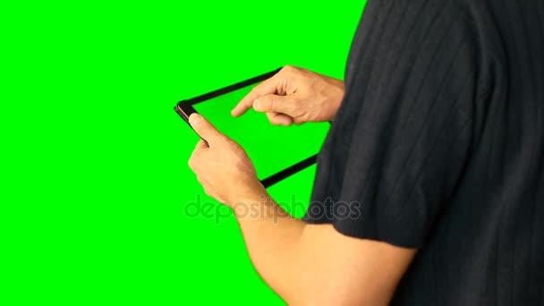 Člověk s použitím tabletu s zelenou obrazovkou zdvojnásobil na velké obrazovce.