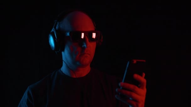 Man in headphones and sunglasses using smartphone in darkness