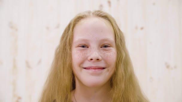 Portrét šťastný červené vlasy dívka s pihami s úsměvem na kameru ve studiu světla. Nadšený dívka teenager se šťastným širokým úsměvem pózuje přední fotoaparát. Zábava, štěstí, úspěch a další pozitivní emoce.