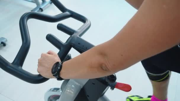 Female hands with fitness watch holding handlebar of indoor bike at cycling class in sport club. Slim woman training on static bike in gym. Fitness woman spinning bike machine.