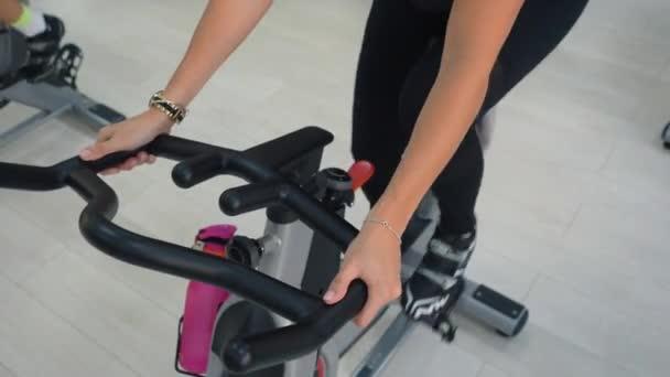 Fitness nő forgó statikus kerékpár kerékpározás órán tornaterem. Portré sport nő lélegzik, miközben kardio edzés beltéri kerékpár fitness klub. Csoport kerékpár tornaterem.