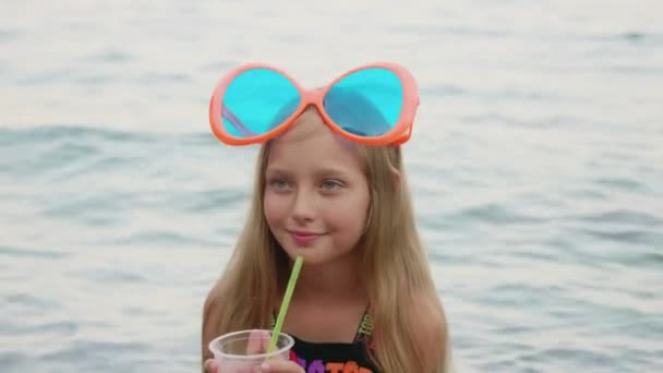 Adorable happy girl drinking cocktail from plastic cup near sea