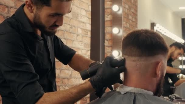Hair dresser using electric shaver for hair cutting bearded man in barber shop. Hairstylist using trimmer for brutal male hairdo. Male hairstyling with electric razor.