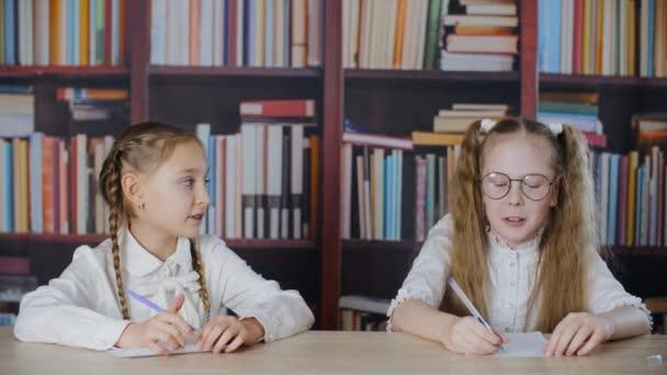 Dvě školačky mluví u stolu ve třídě s knihovnou na pozadí. Šťastný teenager dívka spolužáci mluvit na stole na pozadí knihovny.