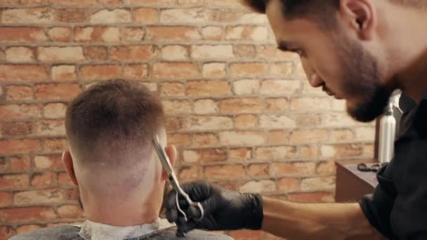 Hair dresser using scissors for hair cutting in barber shop. Hairstylist doing male hairdo with scissors. Male hairstyling with barber accessories close up