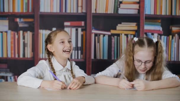 Aranyos, boldog iskolás lányok ülnek az asztalnál és nevetnek az osztályteremben.