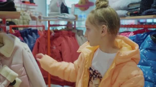 Boldog lány kipróbálás stílusos rózsaszín kabát divat butikban
