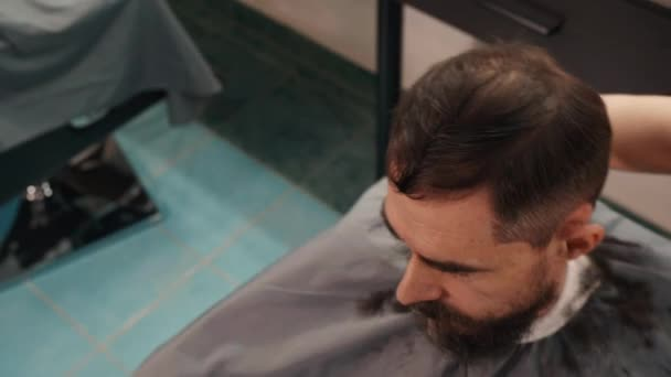 Overhead view of barber turning chair with male client