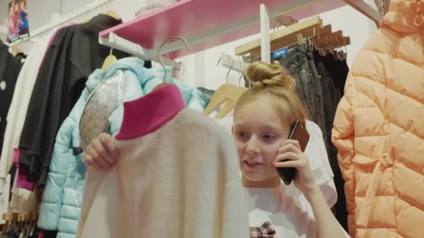Teenager girl choosing clothes and talking mobile at shopping in fashion showroom. Shopper girl looking clothes in shop. Girl teenager calling in clothes store.