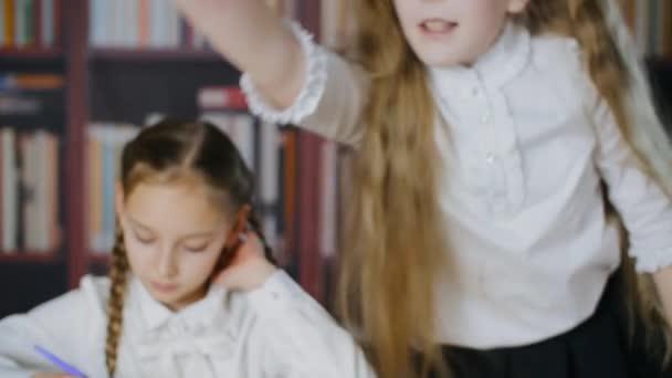 Roztomilá školačka vstává z křesla, mluví a ukazuje