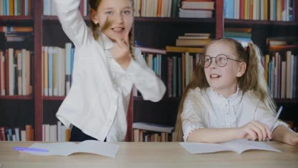 Školačky se spolu baví na školní hodině ve třídě. Legrační teenager dívka ukazuje legrační triky s vlasy copánky. Radostní spolužáci smějící se na knihovně pozadí.