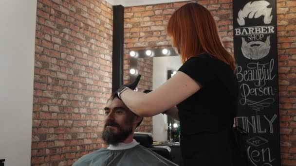 Happy bearded man talking with barber while hair cut in male salon. Hairstylist cutting hair for hipster man in ba.rber shop. Handsome man getting haircut in barbershop