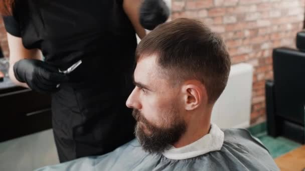 Hairdresser combing and cutting with scissors male hair in barbershop. Bearded man receiving hair cut with comb and scissors in barber salon. Male beauty industry.
