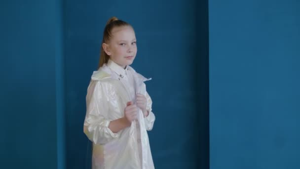 Beautiful teenage girl in fashionable glossy jacket looking at camera