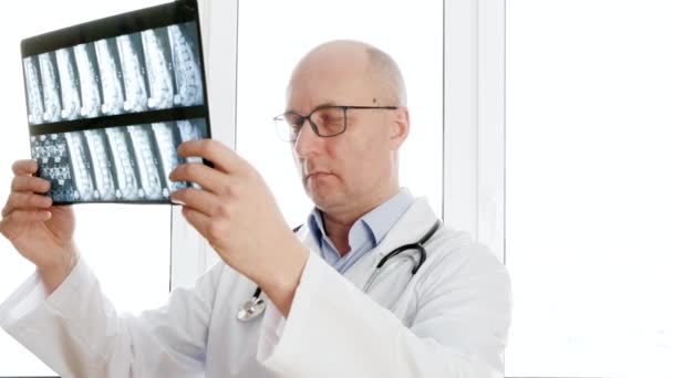 Man surgeon looking backbones x-ray front window in clinic office. Male doctor holding x-ray spine bones looking to camera. Portrait doctor in medical gown with phonendoscope.
