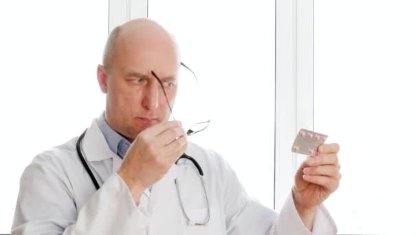 Pharmacist in white coat reading annotation on tablet blister on window background in drugstore. Portrait pharmacist holding in hands drug pills in pharmacy.