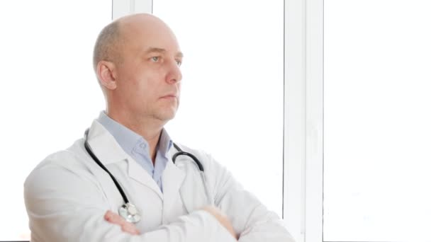 Portrait doctor in white medical gown with phonendoscope looking away on window background. Therapist with stethoscope looking to camera.