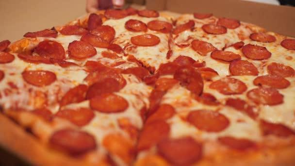 Zblízka ruce s krájenou horkou feferonkovou pizzu. Lidi si berou pizzu v italský pizzerii. Předkrm italské kuchyně, tradiční svačinka a jídlo.