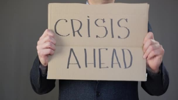 Businessman holding cardboard with crisis ahead inscription