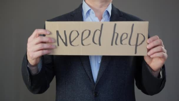 Businessman holding cardboard with need help inscription