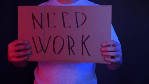Man holding cardboard with need work inscription
